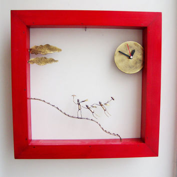Red wooden frame clock with windblown figures, bronze sculpture of men on a wavy ladder with a clock.