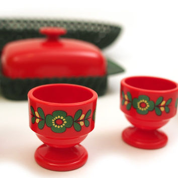 Vintage red plastic egg cups with green butter dish and bread basket. Printed floral design. Emsa West Gremany. 60s /70s