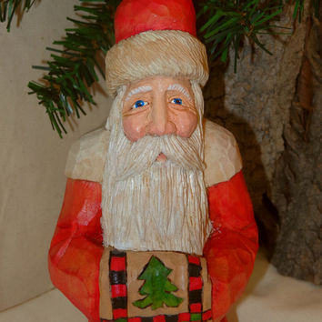 Santa carved wood sculpture, holding a lodge or cabin style quilt with spruce trees and moose by Dan and Debbie Easley