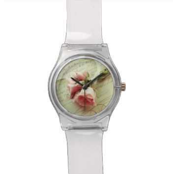 pink roses with ribbon on old handwriting watch