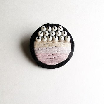 Hand embroidered brooch with light pink colors, shell beads on black muslin with black leather backing An Astrid Endeavor modern embroidery