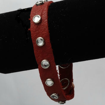 "Genuine silver/gray leather bracelet.  Silver studs.  3 snaps for adjustment. Fits wrists 5"" - 8""."