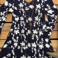 Our Looks Like We Made It Dress is a must have! It's a tunic dress with floral embroidery detail and a v-neckline. Has bell sleeves and cut out back. Side pockets as well.