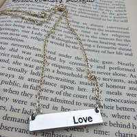 """Silver metal bar with with word """"Love"""" engraved in it and sterling silver chain necklace."""