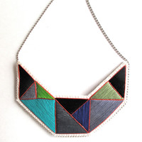 Geometric statement necklace hand embroidered with black, gray, purple, and green colors outlined in red Fall fashion textile jewelry