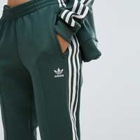 adidas Originals adicolor Three Stripe Track Pants In Green at asos.com