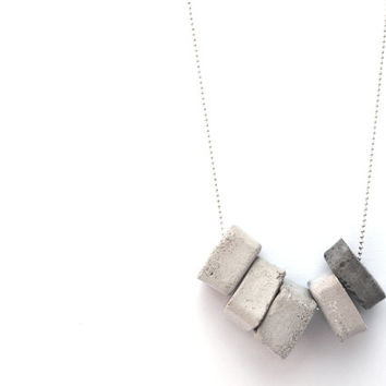 Gray concrete and sterling silver necklace. Five gray concrete medallions varied with white concrete, hangs on delicate 925 silver necklace.