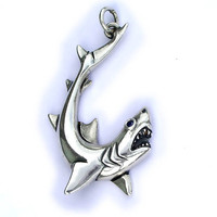 Silver shark pendant set with a natural blue sapphire for its eye.