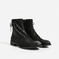 BLACK LEATHER BOOTS WITH ASYMMETRIC FACING DETAILS
