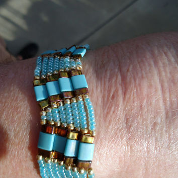 Beaded bracelet in shades of turquoise and gold in zig zag pattern with tila beads and Miyuki seed beads.Handmade