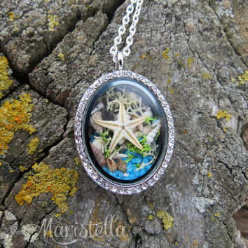 REAL SEASTAR, Real SeaSHELLS, Real corals, Real moss and sand in a two sided glass necklace Mermaid CLOSED locket pendant with silver chain.