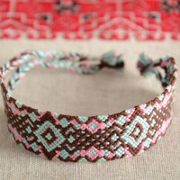 Handmade friendship wrist bracelet woven of threads with colorful ornament