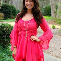 Coral cotton dress with long bell sleeves that is off the shoulders.