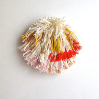 Fiber art brooch using red, cream, light pink, tan and yellow threads hand stitched on cream muslin cream felt back abstract design