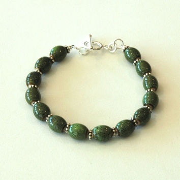 Bracelet with green ceramic beads, silver spacers and silver togggle clasp.