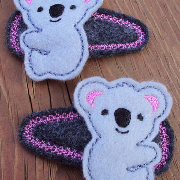 Light Grey felt koala bear on dark grey snap clip covers with a bright pink stiching around the edges.