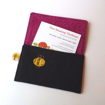 Embroidered card holder with yellow bee design on black linen with speckled berry colour lining
