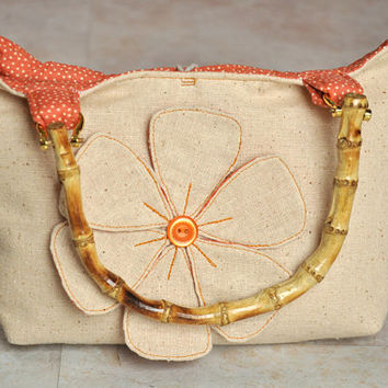 adorable small tan and orange purse with fabric flower and bamboo handles