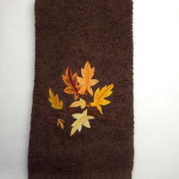 Tree Branch With Fall leaves in beautiful fall colors of yellow orange gold burnt orange embroidered on a brown towel.