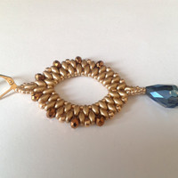 handmade earrings of gold superduo and a blue metallic drop