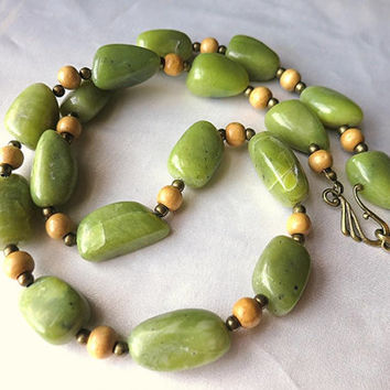 Bold, handmade necklace with olive jade serpentine, wood, and bronze beads. Tropical green, luminous stones. Long, boho statement jewelry.