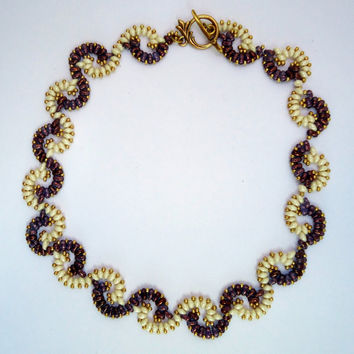 Beaded necklace, choker style in twisted pattern in shades of beige and chocolate brown.