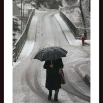 Older Woman Walking In The Snow With An Umbrella, framed black wood, white matte