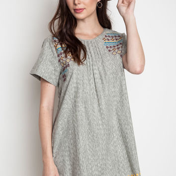 This beautiful lightweight chambray shift dress features pattern embroidered at yoke and bottom hemline, a scoop neckline with pin tack detailing, short sleeve, slit back with single button closured, it's loose fitting and finish with two side of pockets.
