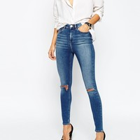 ASOS Ridley High Waist Skinny Jeans in Darmera Mid Stonewash with Busted Knees at asos.com