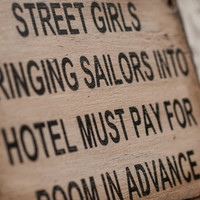 Street girls bringing sailors into hotel must pay for room in advance sign made from reclaimed plywood