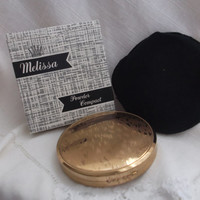 Unused Melissa gold tone compact. Excellent condition, original box, label, sifter, puff & pouch. Ideal gift idea.