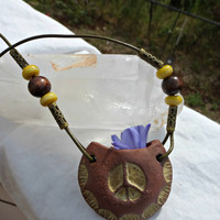 Olive green leather, glass and ceramic pendant vase with peace sign necklace.