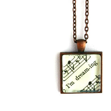 Dreaming necklace jewelry accessory for women made with vintage sheet music under glass with words music notes
