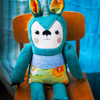 Unicorn  Cornelius with the hand embroidered flowered face . Soft art toy by Wassupbrothers.