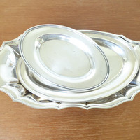 Three small oval silver plate trays with a light patina
