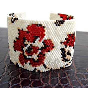 Beaded peyote cuff bracelet with carnations, in cream, red and brown.