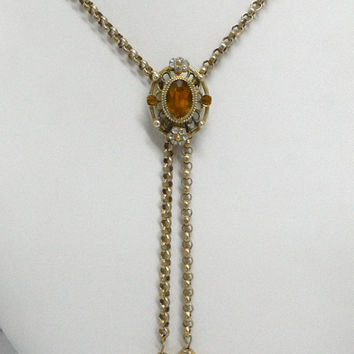 Art Deco slide necklace. Brass lariet 1930s Amber, clear rhinestons, tassels.