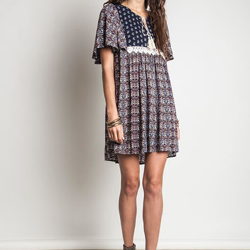 This relax fit baby doll boho dress features mixed floral print, print navy panel at yoke contrast with white crochet lace accents, round neckline with v-cut-out and self-tie rope tassel closured, short cap sleeves, and is finished pleated detailing. Unlin