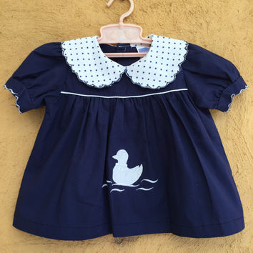 Navy blue vintage baby/toddler dress with polka dot scalloped peter pan collar and duck motif. Size 1/2.