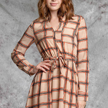 This casual dress features plaid pattern throughout, partial button-up front, v-neckline with low collar, long sleeves with button closure, left breast pocket, flare skirt and finished with elastic waist and self-tie sash. Fully Lined. Pair with over the k