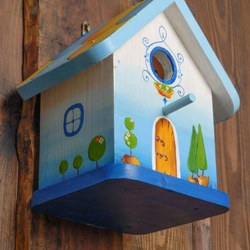 Handmade painted wooden birdhouse in the shape of forest house