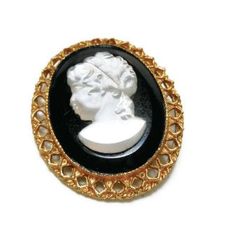 Glass cameo brooch on black glass with gold tone filigree frame