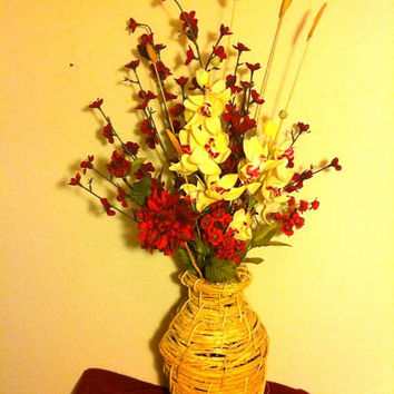 Autumn inspired floral arrangement. Red peonies, garden blossoms and yellow orchids.
