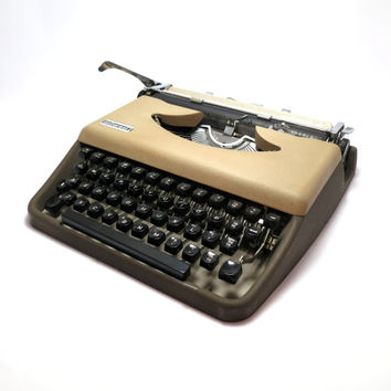 Beige 1950s Portable Typewriter- Antares. In Working Condition and Good Cosmetic Condition. Carry Case