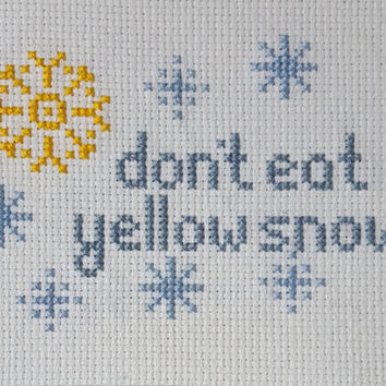 "Cross Stitch ""don't eat yellow snow"" can be purchased loose or with an option of a brown or black frame"