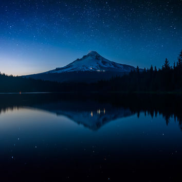 Stars in the night sky and Mount Hood reflecting in Trillium Lake at night, in Mount Hood National Forest, Oregon.