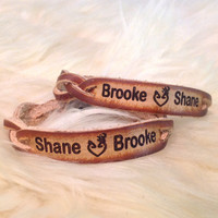 Braided leather Bracelet set of two for a couple to exchange--Names engraved on both and country love heart between