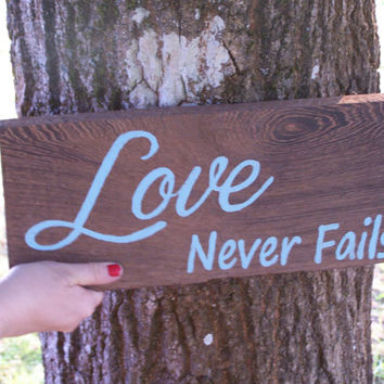 Love Never Fails Sign on a zebra type grainy wood
