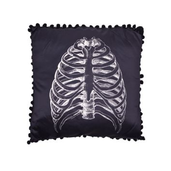 This black satin pillow is trimmed in black pom poms and features an off-white, vintage medical illustration of a ribcage.