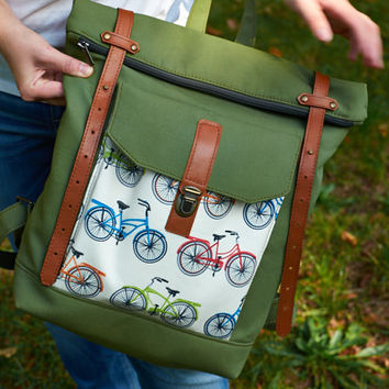 Green canvas backpack with folded top. Big pocket with bike print.